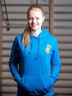 Ein sportliches Mädchen steht vor einer Sprossenwand in einem Fitnessstudio und trägt einen blauen Damen-Kapuzenpullover mit einem orangenen fitterritter Logo.