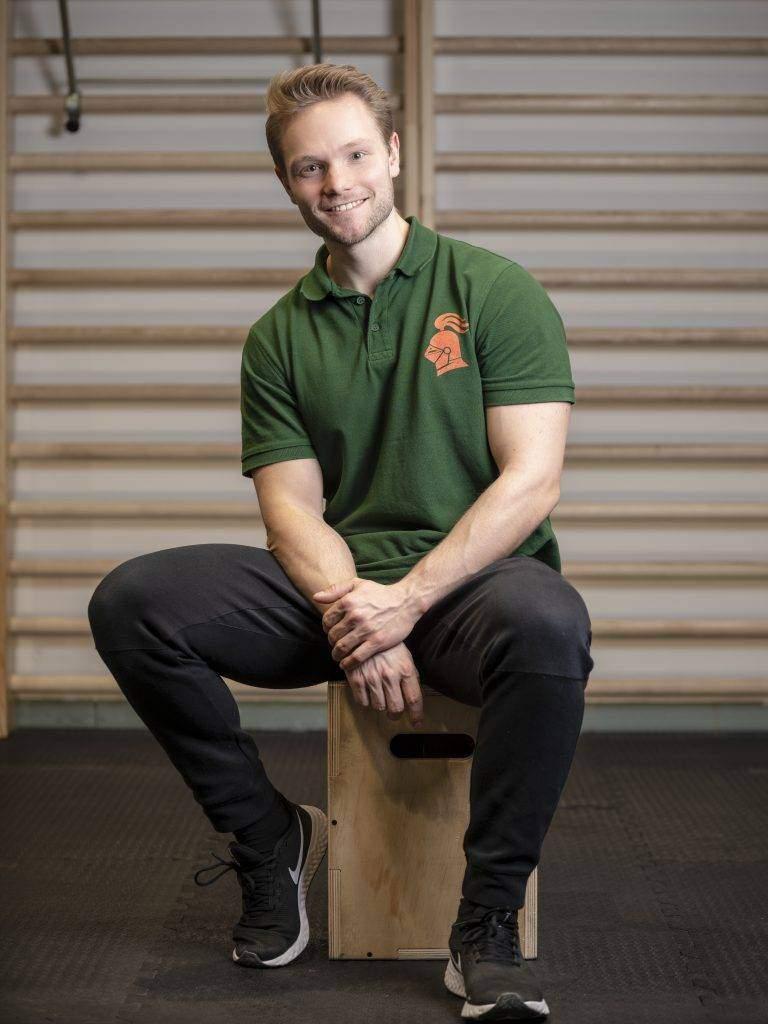 Personal Trainer Jakob Ritter sitzt auf einem Hocker vor einer Sprossenwand. Er trägt ein grünes Herren-Poloshirt mit einem orangenen fitterritter Logo, eine schwarze Trainingshose und schwarze Sportschuhe.