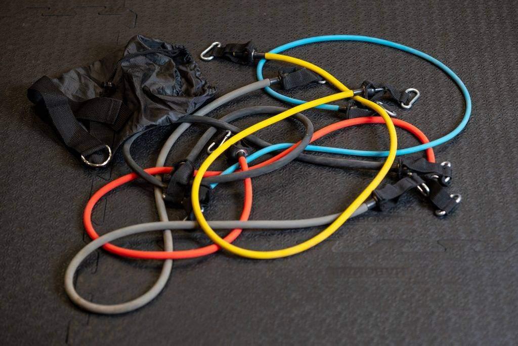Einige bunte fitterritter Resistance Bänder liegen auf dem Boden in einem Trainingsraum. Daneben liegt die Aufbewahrungstasche der fitterritter Resistance Bänder.