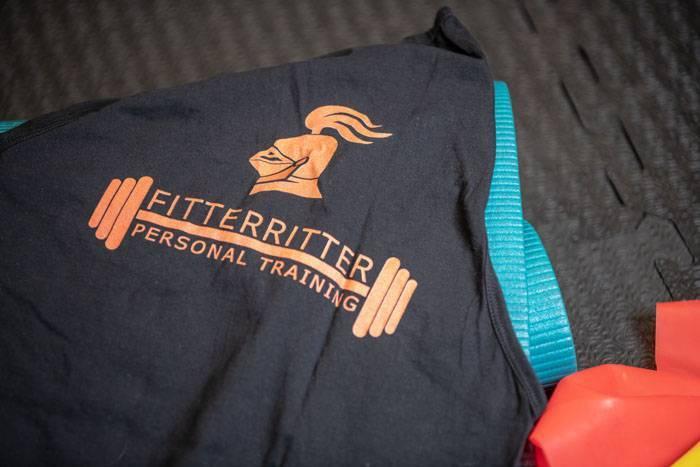 Ein schwarzes Herren-Tanktop mit orangenem fitterritter Logo liegt auf dem Boden neben einer fitterritter Matte und einigen fitterritter Trainingsbändern.