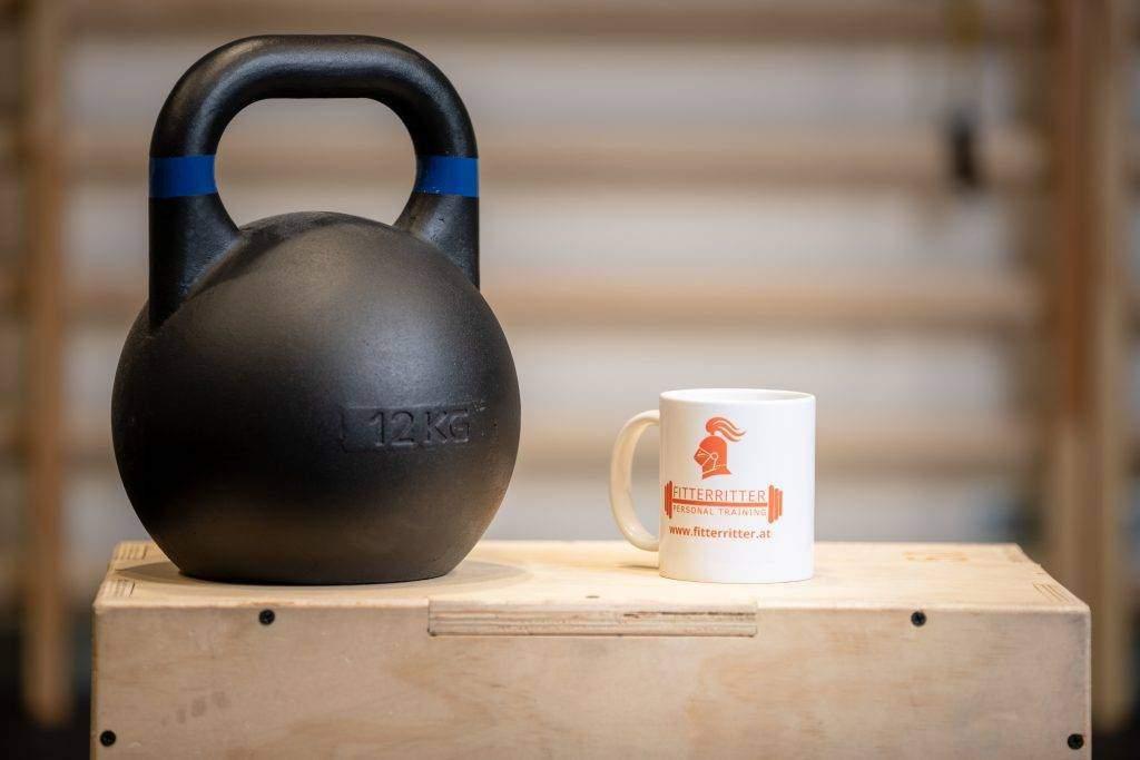 Eine weiße Tasse mit orangenem fitterritter Logo steht auf einem Holztisch in einem Fitnessstudio, daneben befindet sich eine schwarze Kettlebell.