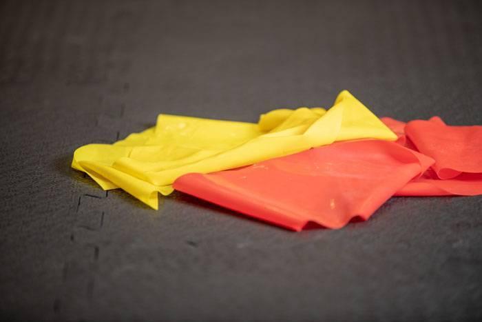 Ein gelbes und ein rotes fitterritter Trainingsband liegen auf schwarzen Trainingsmatten in einem Fitnesscenter.