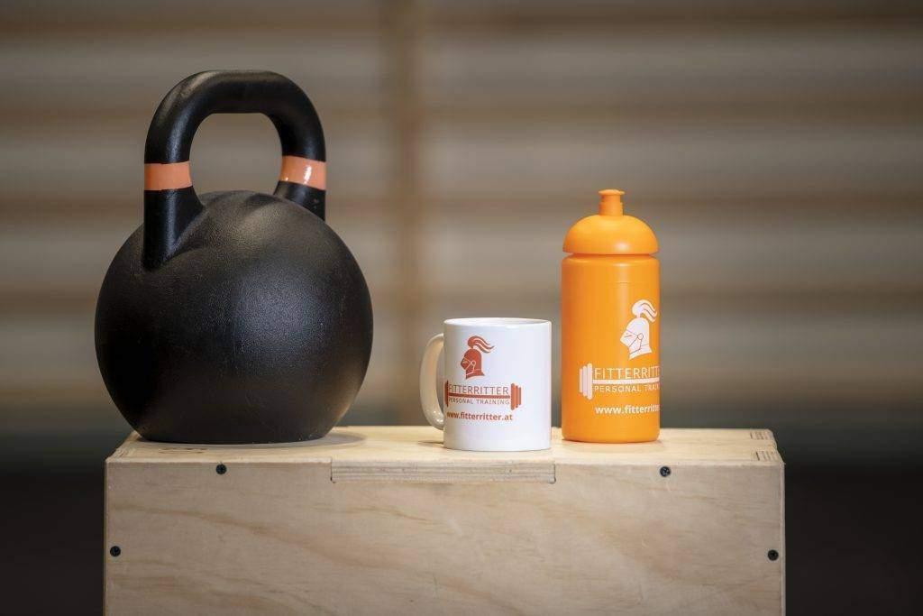 """Auf einem Holztisch in einem Fitnesscenter befinden sich eine weiße fitterritter Tasse und eine orangene fitterritter Trinkflasche. Die Combo tritt unter dem Namen """"Trink dich fit"""" auf."""